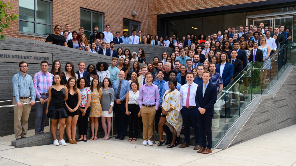 office of residential living professional and student staff in front of healy family student center